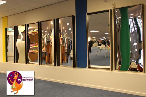 L'application! Dans une aire de jeux intérieure, un mur blanc avec un ensemble complet de miroirs rieurs.